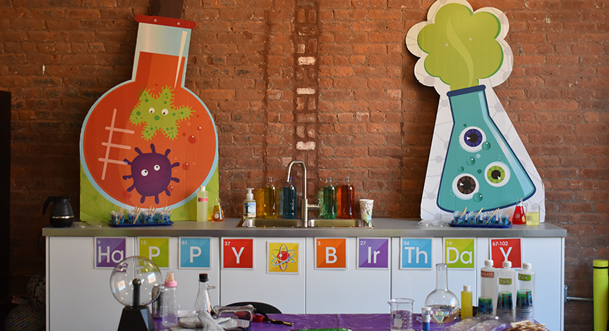 Mad science party room with a table with a purple table cloth and science decoration the background